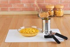 开罐头用具和碗罐装玉米 免版税库存图片