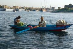 开罗,埃及2017年2月18日:一条小船的另一蹲下两位阿拉伯的渔夫特点尼罗河,一用浆划和 免版税库存图片
