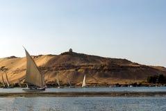 开罗,埃及2017年2月17日:图尔库尼罗河小船称felucca用通过在与t的一个巨大的沙漠沙丘下的游人装载 库存照片