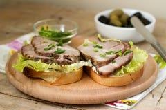 开胃三明治用肉、莴苣和调味汁服务用橄榄 土气样式 免版税库存照片