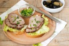 开胃三明治用肉、莴苣和调味汁服务用橄榄 土气样式 免版税图库摄影