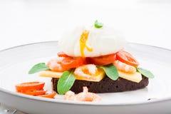开胃三明治用荷包蛋、蕃茄、虾和芝麻菜 免版税库存照片