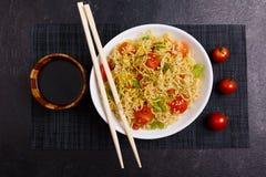 开胃中国面条服务用蕃茄和绿色,在蕃茄、酱油和筷子旁边 免版税库存照片