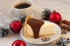 开胃乳酪蛋糕的片断用在它,银色锥体、肉桂条和圣诞节t的熔化巧克力 免版税库存图片