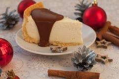 开胃乳酪蛋糕的片断用在它,银色锥体、肉桂条和圣诞节t的熔化巧克力 免版税库存照片