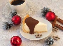 开胃乳酪蛋糕的片断用对此的熔化巧克力,一杯咖啡,银色锥体、肉桂条和圣诞节t 免版税库存图片