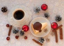 开胃乳酪蛋糕的片断用对此的熔化巧克力,一杯咖啡,银色锥体、肉桂条和圣诞节t 库存图片