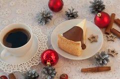 开胃乳酪蛋糕的片断用对此的熔化巧克力,一杯咖啡,银色锥体、肉桂条和圣诞节t 库存照片