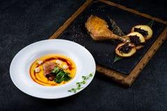 开胃南瓜汤在一块白色板材供食在餐馆 鸭子confit用被烘烤的苹果 免版税库存照片