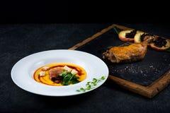 开胃南瓜汤在一块白色板材供食在餐馆 鸭子confit用被烘烤的苹果 免版税图库摄影