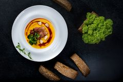 开胃南瓜汤在一块白色板材供食在餐馆 免版税库存图片