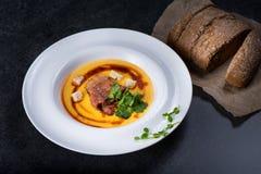 开胃南瓜汤在一块白色板材供食在餐馆 免版税库存照片