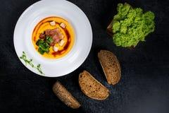 开胃南瓜汤在一块白色板材供食在餐馆 库存照片