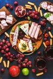 开胃各种各样的开胃菜红色酒,果子,乳酪,在蓝色背景的香肠 意大利或西班牙快餐 看法从 免版税库存照片