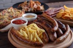 开胃啤酒快餐关闭  与法国fr的烤香肠 免版税库存图片