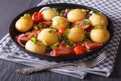 开胃嫩土豆土豆用油煎的烟肉和草本在板材 免版税库存照片