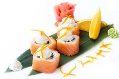 开胃寿司卷用三文鱼和乳脂干酪费城在白色背景的一片香蕉叶子延长 免版税库存图片
