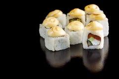 开胃寿司卷用在一个黑背景特写镜头的被烧焦的蛋黄酱 图库摄影