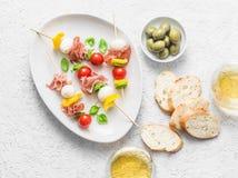 开胃小菜串 喝酒的地中海开胃菜-熏火腿、甜椒、西红柿、无盐干酪乳酪在串和w 免版税库存图片