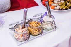 开胃小菜开胃菜一点玻璃瓶子充塞用乳酪希脂乳葱和玉米沙拉的在白色板材 库存照片