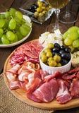 开胃小菜承办酒席盛肉盘用烟肉,生涩,蒜味咸腊肠、乳酪和葡萄 图库摄影