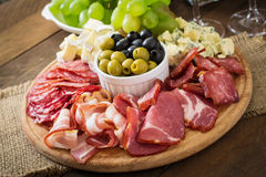 开胃小菜承办酒席盛肉盘用烟肉,生涩,蒜味咸腊肠、乳酪和葡萄 免版税库存图片