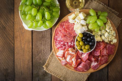 开胃小菜承办酒席盛肉盘用烟肉,生涩,蒜味咸腊肠、乳酪和葡萄 免版税库存照片
