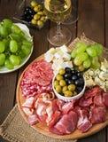 开胃小菜承办酒席盛肉盘用烟肉,生涩,蒜味咸腊肠、乳酪和葡萄 免版税图库摄影