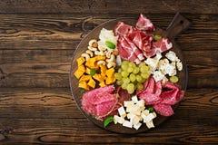 开胃小菜承办酒席盛肉盘用烟肉,生涩,香肠、青纹干酪和葡萄 库存照片