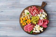 开胃小菜承办酒席盛肉盘用烟肉,生涩,香肠、青纹干酪和葡萄 库存图片