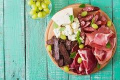 开胃小菜承办酒席盛肉盘用烟肉,生涩,香肠、青纹干酪和葡萄 免版税图库摄影