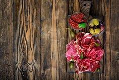开胃小菜承办酒席盛肉盘用烟肉,生涩,香肠和橄榄 图库摄影