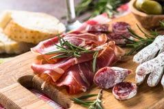 开胃小菜熟食-切的肉、火腿、蒜味咸腊肠和橄榄  库存照片