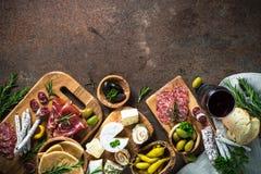 开胃小菜熟食-肉、乳酪、橄榄和酒在石头 免版税库存图片