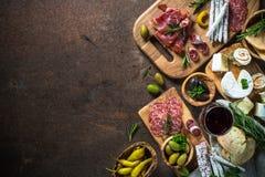 开胃小菜熟食-肉、乳酪、橄榄和酒在石头 库存图片