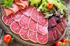 开胃小菜用火腿、蒜味咸腊肠和bresaola 蕃茄和蓬蒿 selec 库存照片