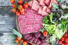 开胃小菜用火腿、蒜味咸腊肠和bresaola 蕃茄和蓬蒿 selec 免版税库存图片
