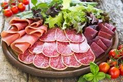 开胃小菜用火腿、蒜味咸腊肠和bresaola 蕃茄和蓬蒿 selec 库存图片