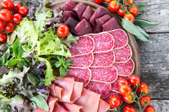 开胃小菜用火腿、蒜味咸腊肠和bresaola 蕃茄和蓬蒿 selec 图库摄影