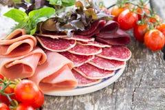 开胃小菜用火腿、蒜味咸腊肠和bresaola 蕃茄和蓬蒿 selec 免版税库存照片