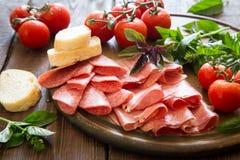 开胃小菜用火腿、bresaola和蒜味咸腊肠 面包、蕃茄和蓬蒿 免版税图库摄影