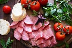 开胃小菜用火腿、bresaola和蒜味咸腊肠 面包、蕃茄和蓬蒿 免版税库存图片