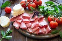 开胃小菜用火腿、bresaola和蒜味咸腊肠 面包、蕃茄和蓬蒿 库存图片