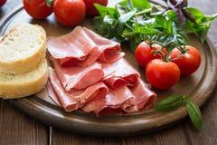 开胃小菜用火腿和bresaola 蕃茄和蓬蒿 有选择性的foc 免版税图库摄影