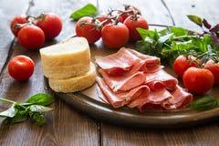 开胃小菜用火腿和bresaola 蕃茄和蓬蒿 有选择性的foc 免版税库存照片