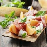 开胃小菜用瓜、无盐干酪、火腿和蓬蒿 图库摄影