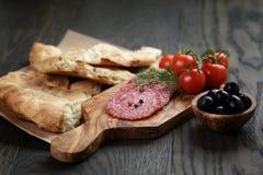 开胃小菜用蒜味咸腊肠、橄榄、蕃茄和面包 免版税图库摄影