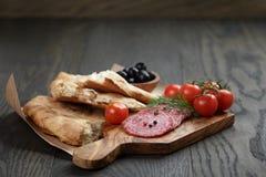 开胃小菜用蒜味咸腊肠、橄榄、蕃茄和面包 免版税库存照片