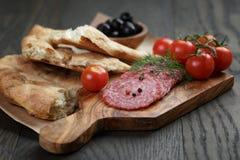 开胃小菜用蒜味咸腊肠、橄榄、蕃茄和面包 免版税库存图片
