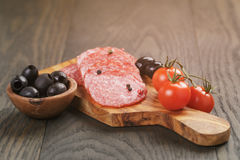 开胃小菜用蒜味咸腊肠橄榄和蕃茄在木头 库存照片